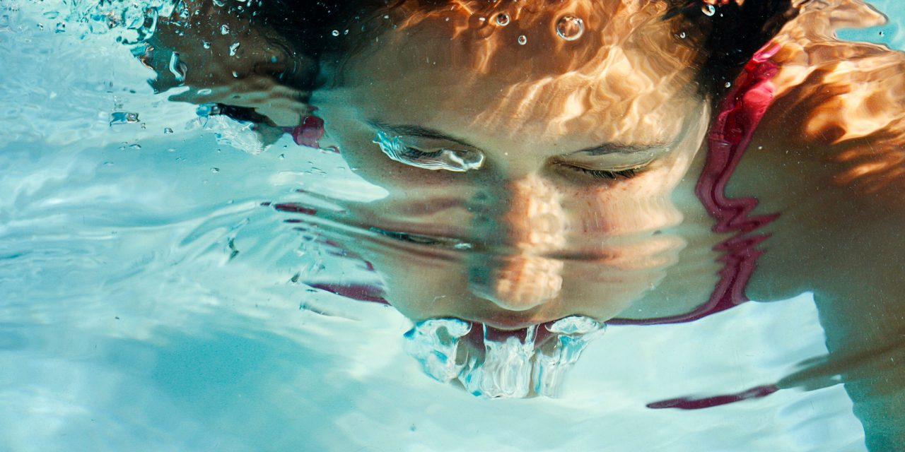 barn svømmer under vann